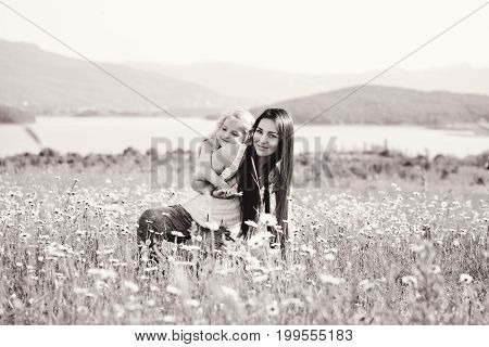 mother and daughter in field of daisies
