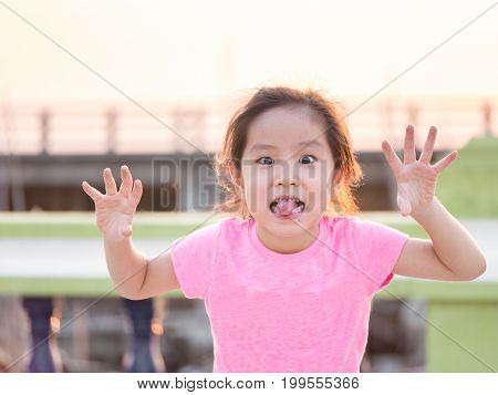 Young cute cheeky girl holding hands up with five fingers wearing pink t shirt sticking out her tongue for funny face