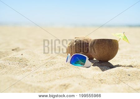 Sunglasses and coconut with drink on sand on the beach, with ocean on background. Perfect vacation.