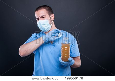 Medic Wearing Face Mask Holding Bad Smelling Water