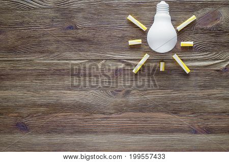 Concepts of business education and innovation. Light bulb on the wooden background flat lay.
