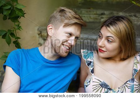 True genuine feelings people love and relationships concept. Outdoor summer shot of cute blonde girl wearing red lipstick spending nice time in park with her handsome cheerful bearded boyfriend