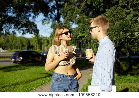 Picture of cute couple drinking coffee outdoors standing and talking against green trees bakground. Beautiful stylish young man and woman having first date in city park enjoying coffee-to-go