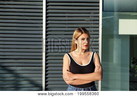 People and modern urban lifestyle concept. Trendy-looking young blonde woman of European appearance standing outdoors against office building background keeping arms folded having confident look
