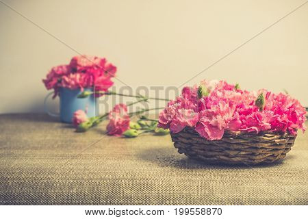 Bright pink carnations flower on small basket  . Vintge image style.