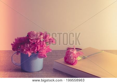 Bright Pink Carnations Flower In Blue Cup, On Classic Paper Book On Table . Vintge Image Style
