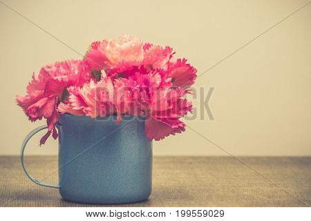 Bright Pink Carnations Flower In Blue Cup On Table . Vintge Image Style