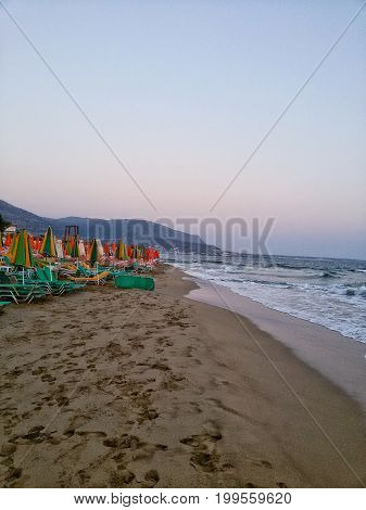 View on a Beach with Sunshades and Deckchairs in the Morning. Close-up of a deserted Beach of Crete.