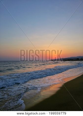View on a beautiful warm Sunrise at the Beach. Enjoy the rising Sun of a new Day. The red Light of a Sunrise is shining on the Waves of a Beach.