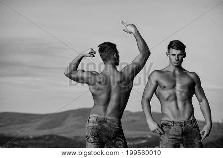 Twin men or bodybuilders athletes show sexy muscular torsos with six packs abs biceps triceps outdoor in mountains on sky black and white