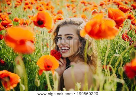 opium. poppy seed and happy girl with long curly hair in red flower field with green stem on natural background summer spring drug and love intoxication