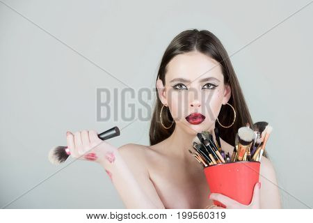 Cosmetics and skincare. Woman has stylish long hair with brush. Girl with fashionable makeup. Beauty salon and fashion.