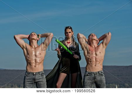 Group of people on blue sky. Beauty and fashion. Bandit gang have conflict. Woman with baseball bat and men. Men and sport or criminal girl outdoor.