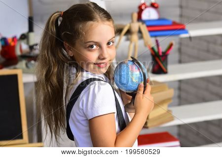Kid Studies Geography. Schoolgirl Holds Little Globe Model