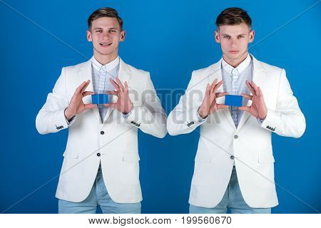 Men holding blank cards with happy and serious faces. Banking and saving concept. Business communication and meeting. Cooperation and partnership. Businessmen wearing white jackets on blue background.