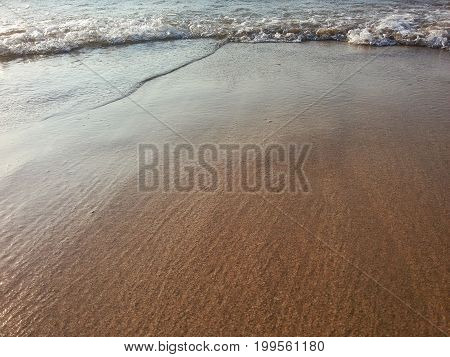 View on a Beach covered by Crystal clear Water. Close-up of a Beach in Summer. Peaceful Ocean waves at Beach. Natural Background.