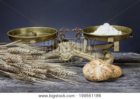 Vintage kitchen scales with scoop of flour are standing on the old wooden desk. The bundle of corn and pastry lies in the foreground.