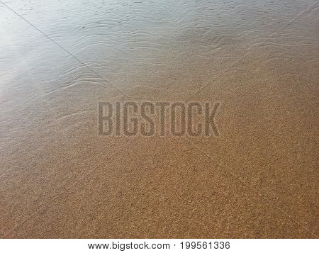 View on a Beach covered by Crystal clear Water. Close-up of a Beach in Summer. Natural Background.