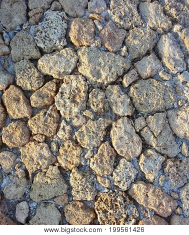 View on heat conducting Stones of a House. Close-up of a Stone Wall. Sunlight falls on Stones. Natural Stone Background