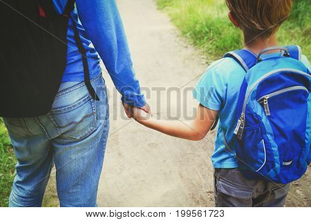 father holding hand of son while going to school