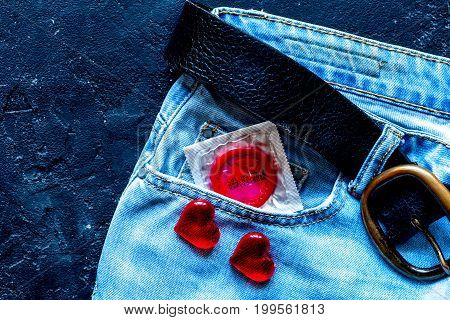 concept male contraception condom in jeans pocket top view.