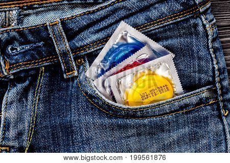 concept male contraception condom in jeans pocket.