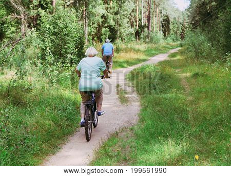active senior couple riding bikes in summer nature
