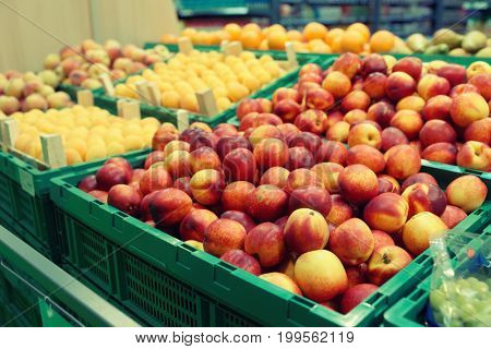 Peaches and apricots in plastic crates, supermarket food store, toned image