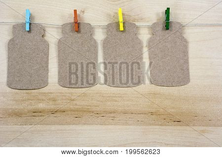 Four colorful clothespins on the rope with notes on the wooden background