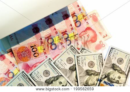 Checking One Hundred Dollar And Yuan Banknotes With Ultraviolet Light Or Black Light Machine On Whit