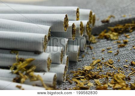 Cigarettes close-up on a gray background with scattered tobacco. side view