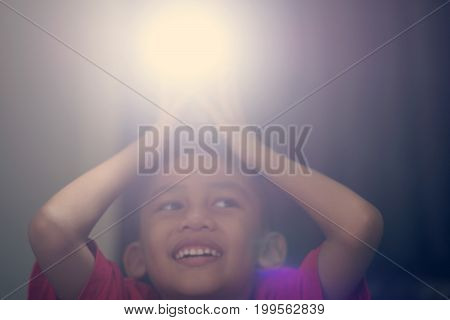 A boy holding a camera flash on his head and smiles happily.