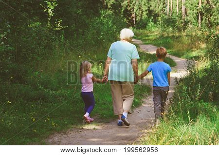 grandmother with kids- little boy and girl- walk in nature