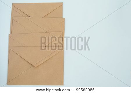 several envelopes from brown letter paper, on white background close-up, top view flat lay