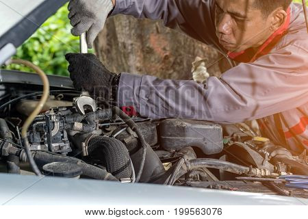 Car mechanic in grey uniform are using a wrench nut at the engine of the car for maintenance Automotive industry and garage concepts.