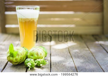 Noni fruit and noni juice and blossom on old wooden table.Horizontal