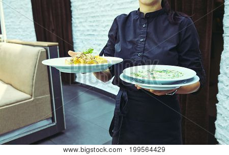 Waiters carrying plates with meat dish at a wedding.