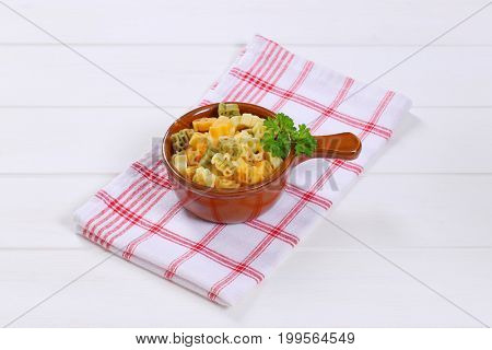 saucepan of cooked colored pasta on checkered dishtowel