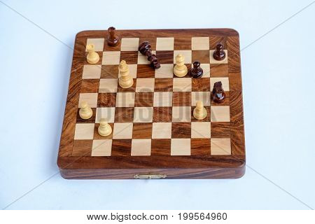 Chessboard with figures in progress isolated over the white background.