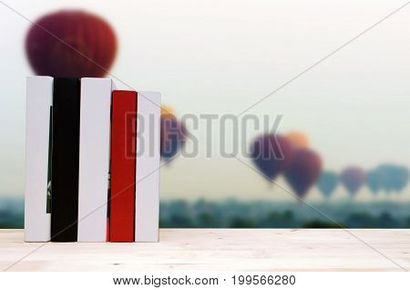 stack book on desk no labels blank spine with blurred view of hot air balloon in the sky background education back to school history landscape nature concept selective focus copy space