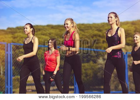 A group of 5 healthy young girls running around in the park. Young women go in for sports. The concept of a healthy lifestyle.
