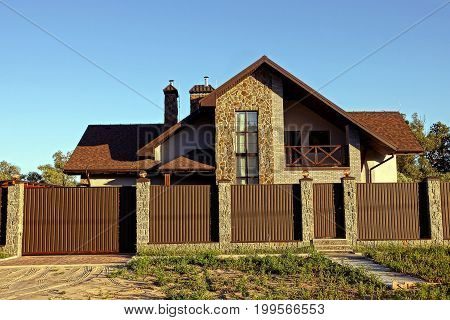 Private house behind an iron fence against the sky
