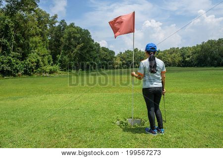 Asian black long hair standing beside golf pole in golf course with sunny day