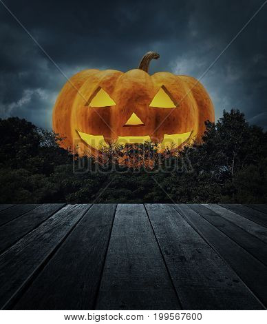 Jack O Lantern pumpkin with old wooden table tree over spooky cloudy sky Horror background Halloween concept