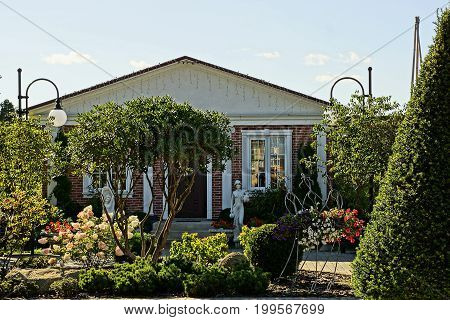 Private house in the garden with ornamental plants and flowers with statues at the doorstep