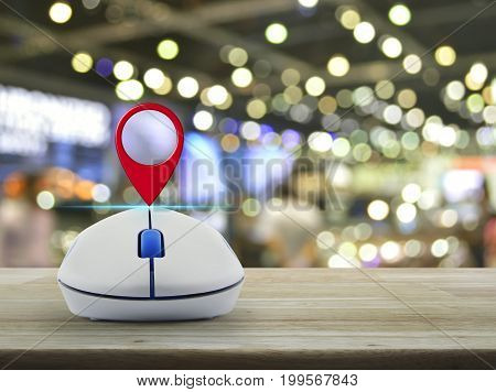 Map pin location button with wireless computer mouse on wooden table over blur light and shadow of shopping mall Shopping navigation concept