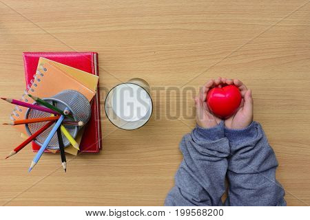 Child's hands holding red heart and notebook with color pencil and milk on wood en table.