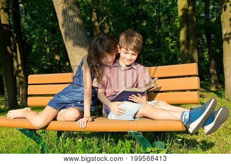 Boy and girl are sitting close to each other on a bench in the park reading one book and smiling. Concept of love and mutual understanding between siblings.