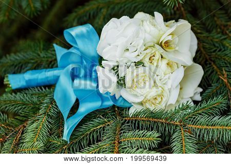 Wedding bouquet . The bride's bouquet. A bouquet of white flowers, and greenery with ribbon colour of Marsala lies on the branches of spruce