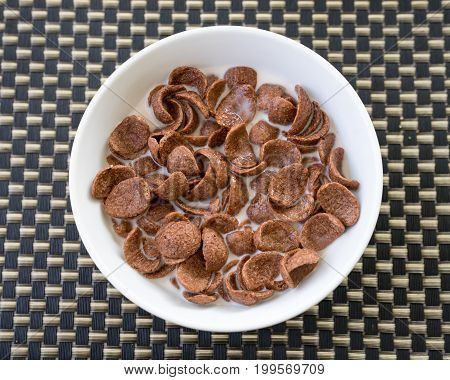 Bowl with chocolate cornflakes on wooden background
